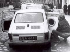 Pesukonetta lastataan pikku-Fiatin kyytiin. Logistiikan pieni ihme.